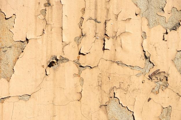 Textura da parede rachada velha amarela da pedra ou do cimento na luz solar para o teste padrão, a parede ou o 3d. horizontal, close-up