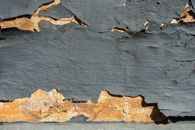 Textura da parede rachada velha cinzenta da pedra ou do cimento na luz solar para o teste padrão, a parede ou o 3d. horizontal, close-up