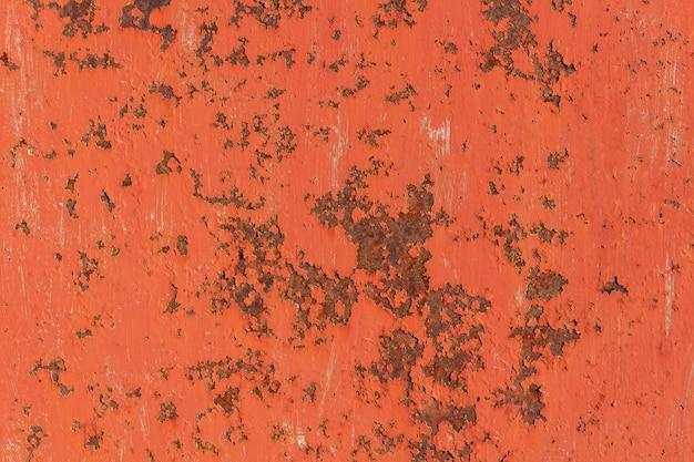 Textura da placa de metal oxidada velha com pintura rachada vermelha com riscos.