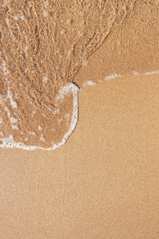 Textura da praia. alinhe a espuma de água sobre a areia limpa.