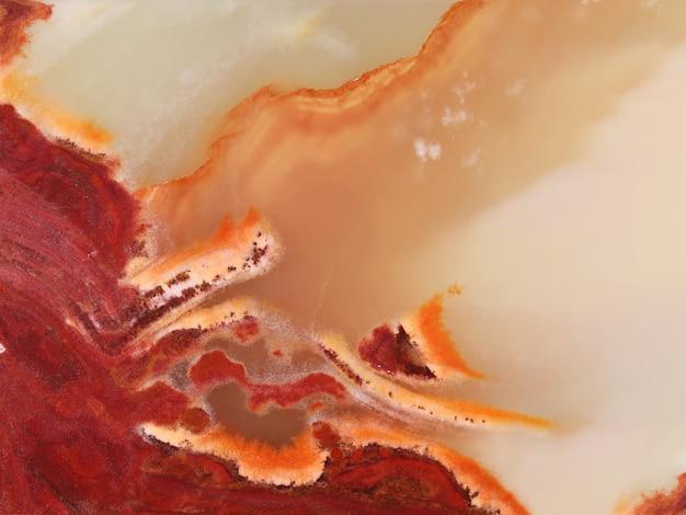 Textura da superfície polida de pedra natural, mármore ônix amarelo-vermelho