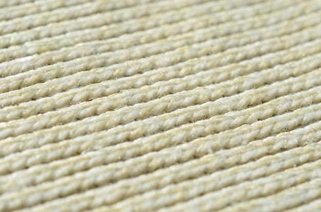 Textura da tela de uma camisola feita malha amarela macia. imagem macro da estrutura de encadernações em fios