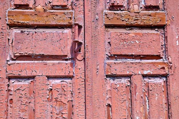 Textura da velha porta descascando tinta em portas de madeira como um detalhe