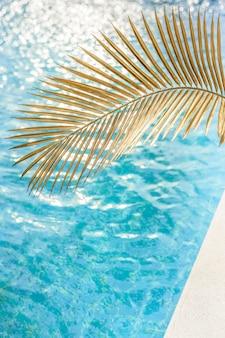 Textura de água azul em uma piscina com folha de palmeira