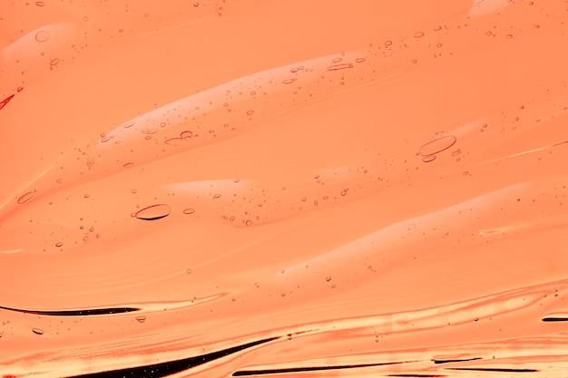 Textura de amostra cosmética transparente de creme gel laranja com fundo de bolhas