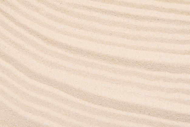 Textura de areia, linhas abstratas no topo de um fundo de areia macia