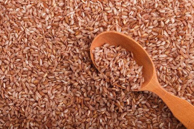 Textura de arroz integral não polido com colher de pau. vista superior, close-up.