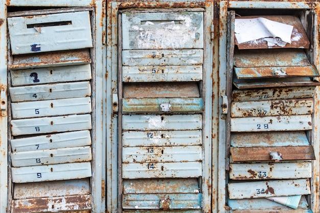 Textura de caixas de correio velhas e enferrujadas com fechaduras e figuras