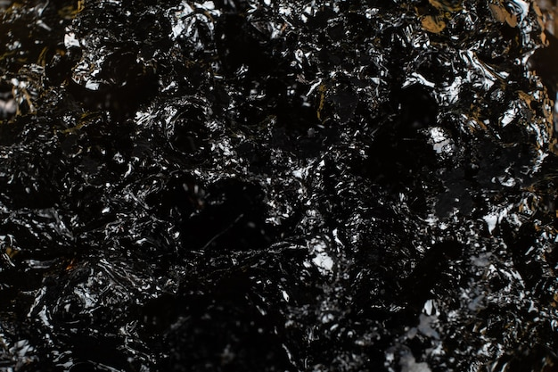 Textura de carvão preto brilhante, fundo escuro.