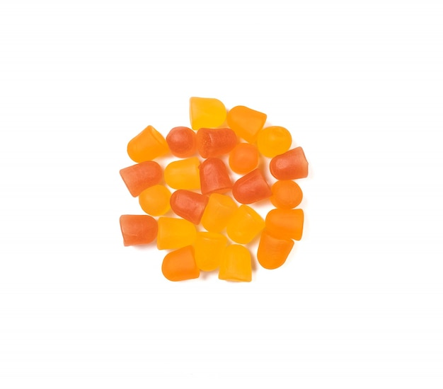 Textura de close-up de gomas multivitamínicas laranja e amarelas sobre fundo branco. conceito de estilo de vida saudável.