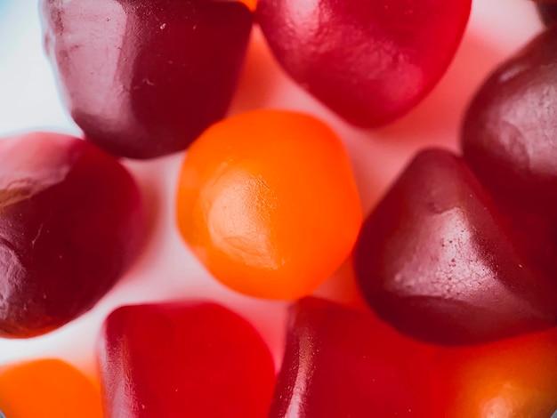 Textura de close-up de gomas multivitamínicas vermelhas, laranja e roxas. conceito de estilo de vida saudável.