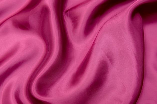 Textura de close-up de tecido vermelho ou rosa natural ou tecido da mesma cor. textura de tecido de algodão natural, seda ou lã, ou material têxtil de linho. fundo de tela vermelho e laranja.