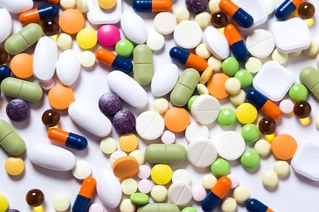 Textura de comprimidos multicoloridos e cápsulas em fundo branco