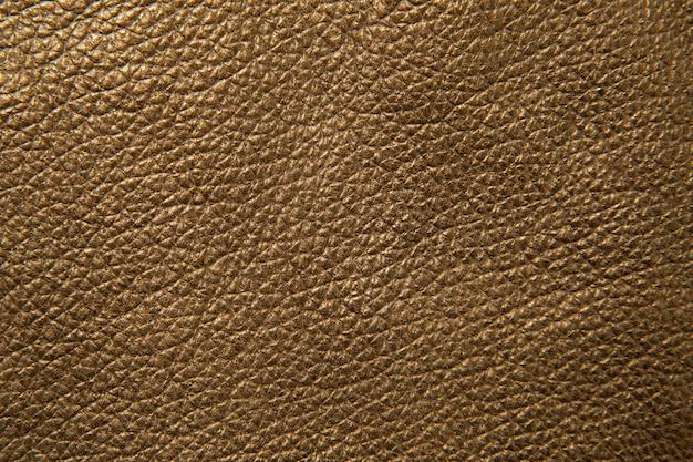 Textura de couro pintado de dourado. superfície artística.