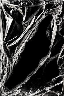 Textura de envoltório de plástico enrugada em um fundo preto