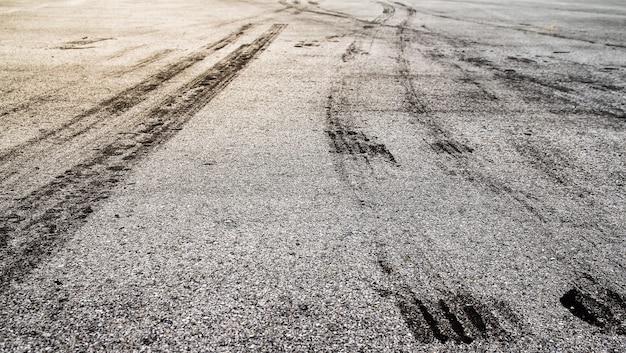 Textura de estrada de asfalto com faixas de pneu escuro na estrada de asfalto