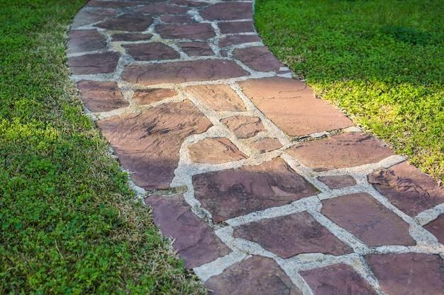 Textura de estrada de pedras de pavimentação no parque de verão.