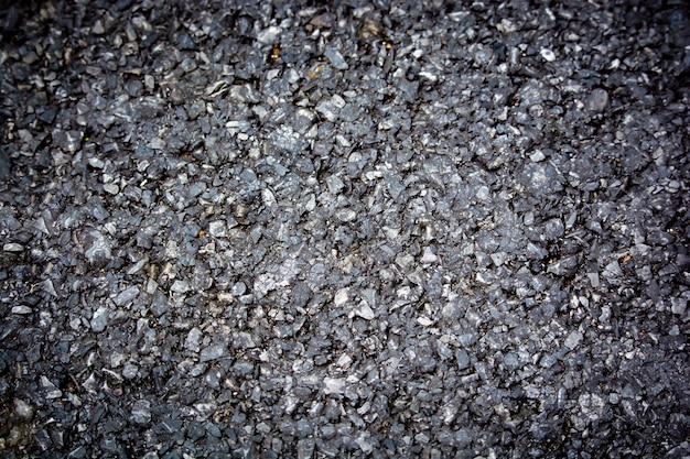 Textura de estrada pavimentada com asfalto vista superior de fundo a textura de migalhas de minerais de superfície de pedra preta