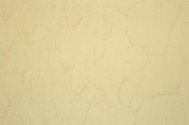 Textura de estuque velho amarelo com rachaduras fundo de parede de estuque rachado