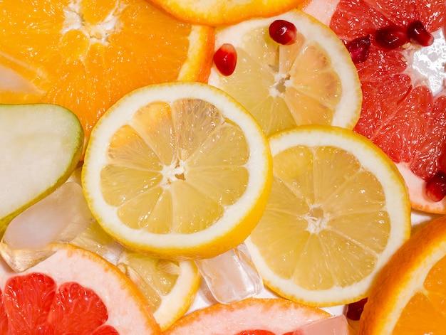 Textura de fatias de frutas, como limão e laranja, romã e toranja com gelo. conceito de verão