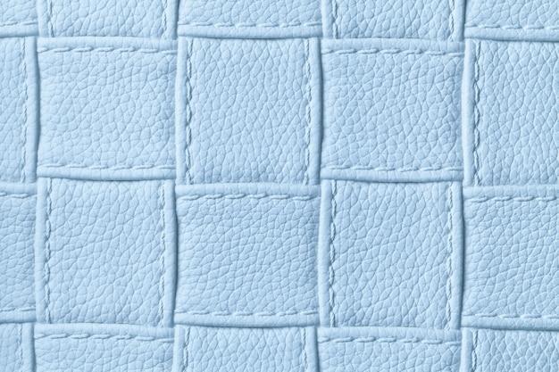 Textura de fundo de couro azul claro com padrão de quadrados e pontos, macro.