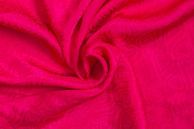 Textura de fundo de tecido de cetim rosa com corações. amo fundo. dia dos namorados.
