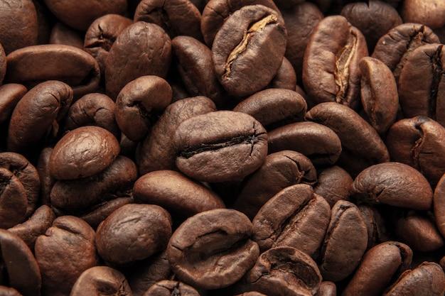 Textura de fundo de um grande número de grãos de café torrados marrons perfumados e frescos. macro