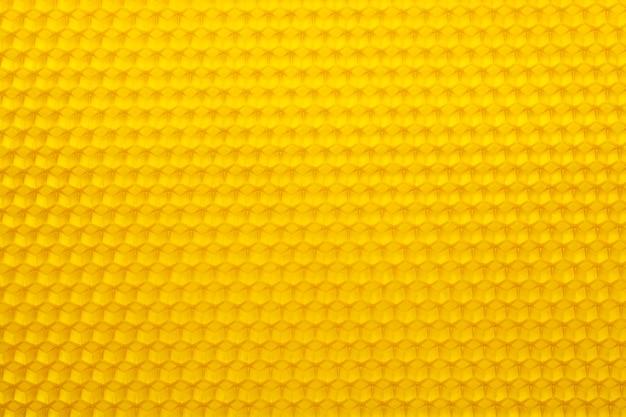 Textura de fundo de uma seção de favo de mel de cera de uma colmeia. conceito de apicultura.