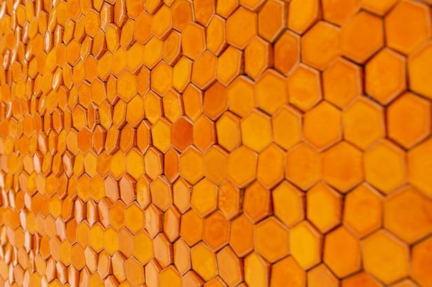 Textura de fundo de uma seção transversal de célula de cera de colmeia. fundo geométrico laranja com favos de mel