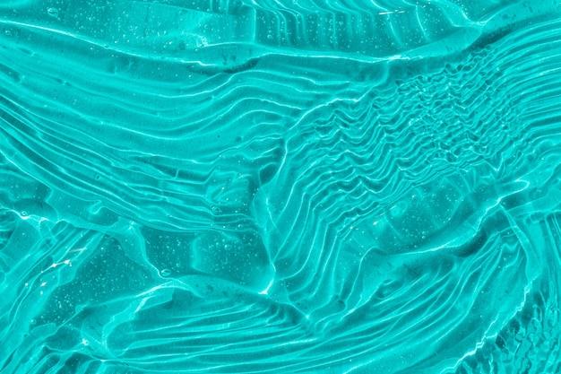 Textura de gel cosmético azul com bolhas transparentes creme para a pele e fundo de soro hidratante facial