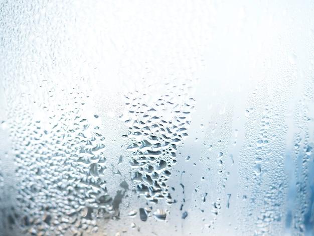 Textura de gotas de água da natureza de close-up em vidro com fundo azul desfocado. umidade do ar causando vapor no vidro.
