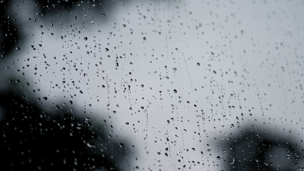 Textura de gotas de chuva na moldura da janela de vidro da sala de café e da natureza