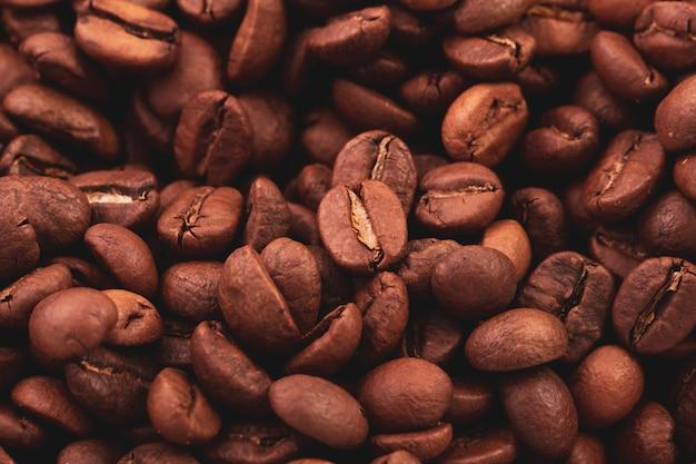Textura de grandes grãos de café torrados, vista superior.