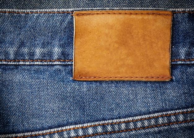 Textura de jeans velho com fundo de etiqueta de couro close-up
