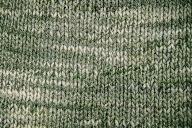 Textura de lenço de lã verde close-up. fundo de malha de malha com um padrão de relevo. tranças em padrão de tricô à máquina