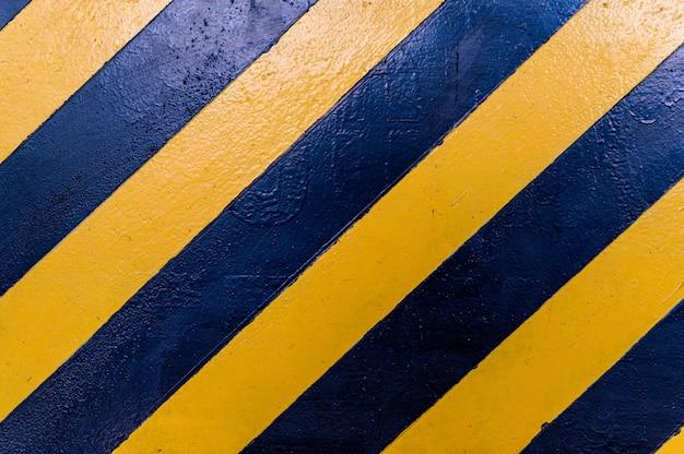 Textura de listras pretas e amarelas na parede. fundo sujo de perigo ou perigo.
