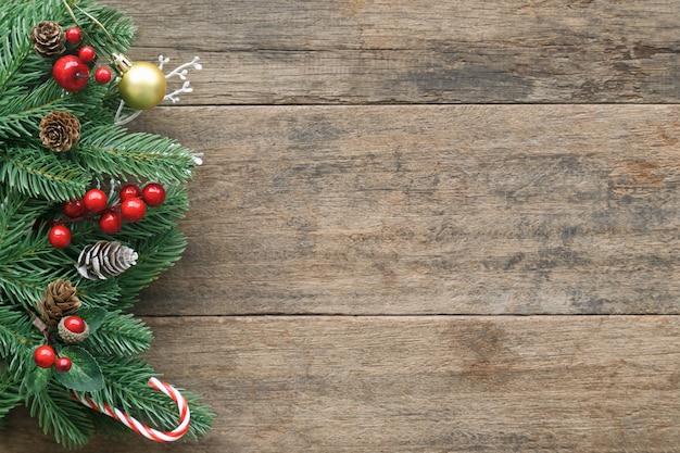 Textura de madeira antiga em branco decorar com folhas de pinheiro e cone, bolas de azevinho, bola de ouro e pirulito.