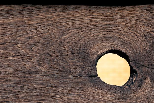 Textura de madeira com um buraco de um nó solto.