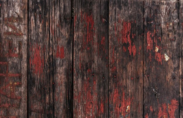 Textura de madeira marrom com resíduos de tinta rachada.