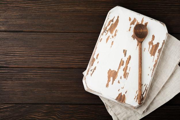 Textura de madeira marrom com velha tábua de cortar e colher de pau. fundo. vista do topo.