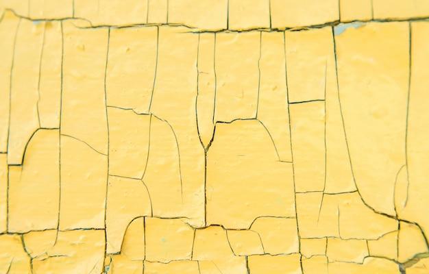 Textura de madeira velha com tinta amarela com rachaduras