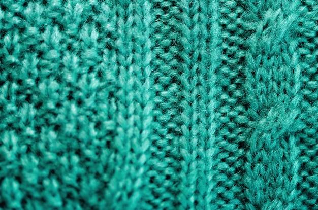Textura de malha. tecido padrão feito de lã. fundo turquesa, espaço de cópia