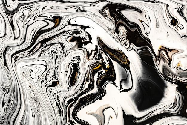 Textura de mármore preto e branco com muitos veios contrastantes dourados.
