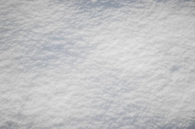 Textura de neve com sombras claras, fundo de inverno
