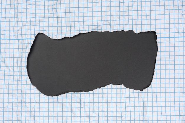 Textura de papel branco amassado em uma gaiola, linhas azuis, bordas rasgadas em um fundo preto