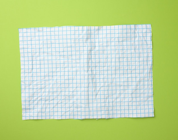 Textura de papel branco amassado em uma gaiola, linhas azuis, superfície verde