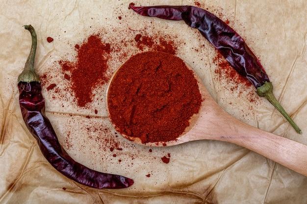 Textura de papel com páprica vermelha na colher de pau e pimenta seca