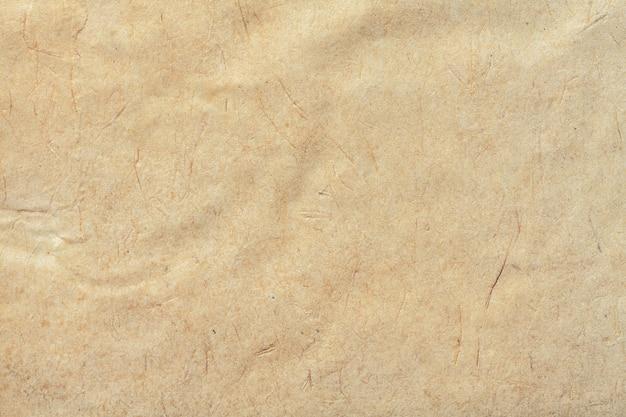 Textura de papel velho bege, fundo amassado. superfície de grunge marrom vintage. estrutura de papelão de pergaminho artesanal.