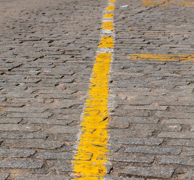 Textura de paralelepípedos cinza escuros com faixa amarela como marcação de estrada