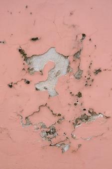 Textura de parede antiga, descascando o fundo de tinta rosa
